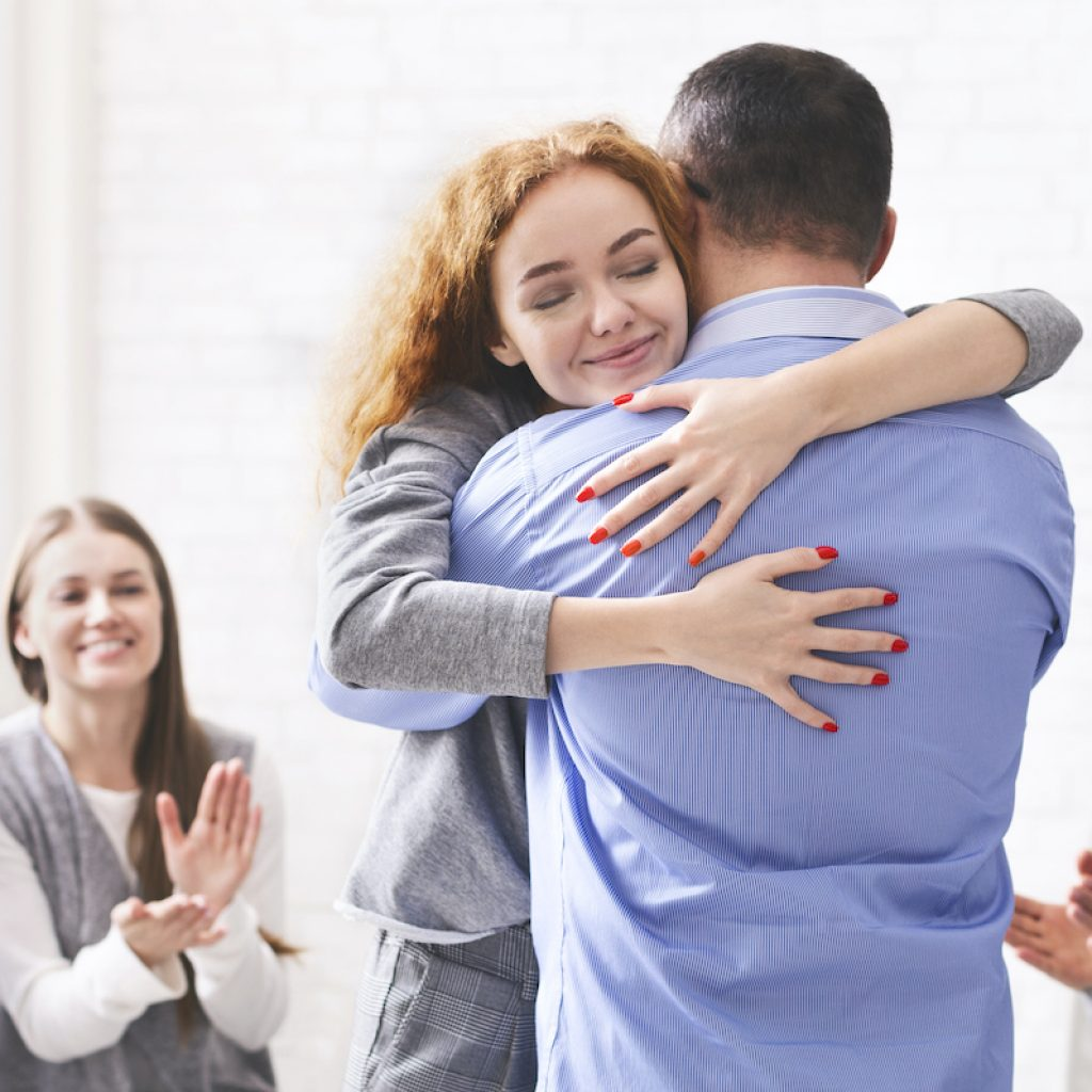 Family Reunion. Happy Couple Hugging After Successful Group Therapy In Marriage Counsellor's Office, Panorama With Free Space
